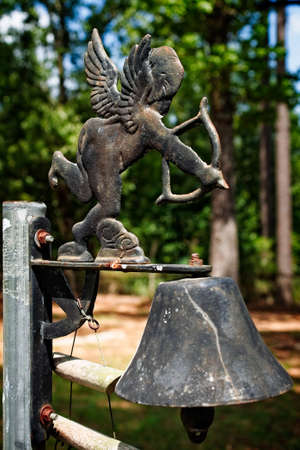 Conroe TX USA - Aug 17, 2017 -   Cupid and a Bell in an old Cemetery.