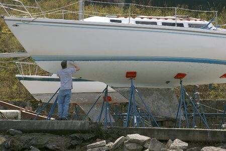 Man works on a sailboat.