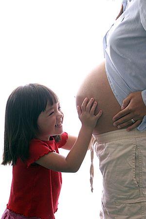 Chica ríe como mamá toca la barriga embarazada.  Foto de archivo - 1954571