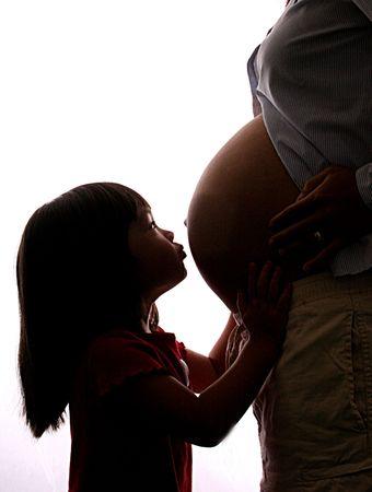 Little girl kisses mommys pregnant tummy.