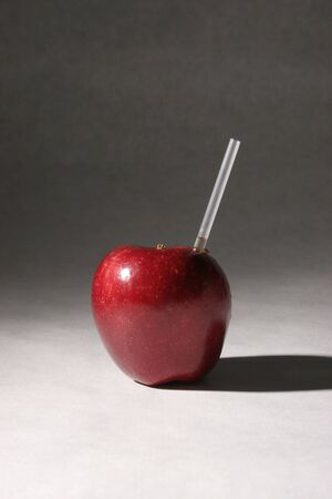 An apple with a straw in it. photo