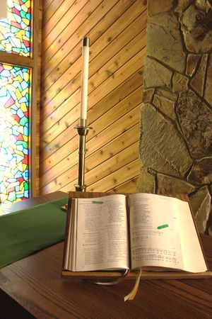 An opened bible and a candle.