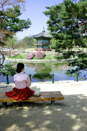 Korean lady sits on a bench in a park.