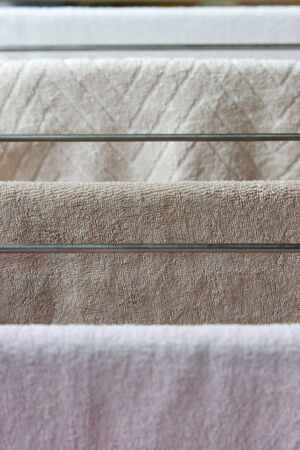clothes rack: Towels drying on a clothes rack.