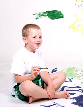 expresses: A young boy expresses his happiness while painting.