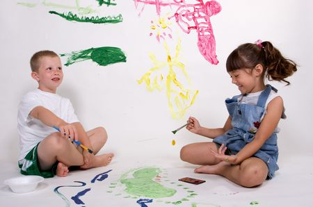 mess: Two kids are having fun painting pictures.