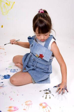A girl makes handprints using paint on white paper. Stok Fotoğraf
