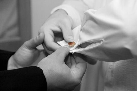 cuff link: An extra pair of hands help the groom with the cufflinks.