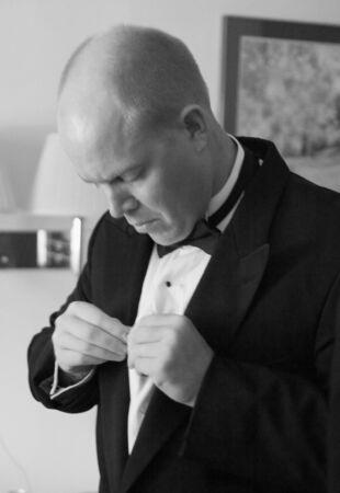 The groom makes last minute adjustments. photo