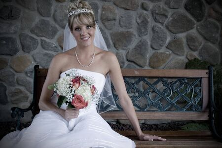 A portrait of a bride sitting on a bench. Stock Photo - 3588551