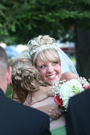 The happy bride hugs a guest after the ceremony. Stock Photo - 3588553