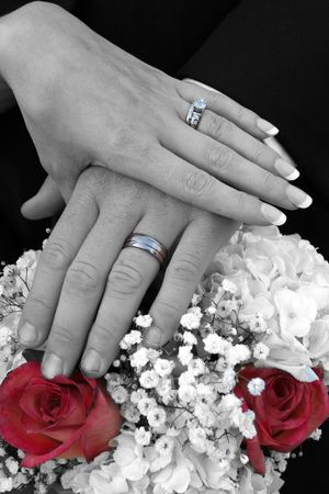 The newlyweds display their wedding rings over a bouquet.