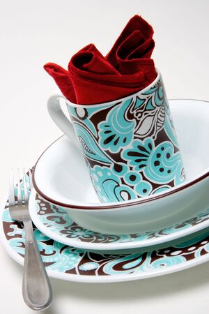 A cup, bowl, napkin, fork, and two plates. photo