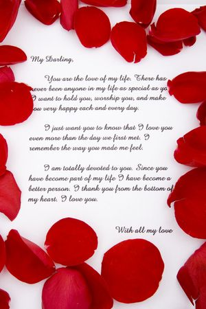 love confession: A romantic love letter with rose petals. Stock Photo