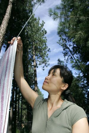 A woman hangs freshly washed clothes on a clothes line. photo