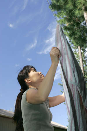 Asian woman hangs laundry on a clothes line. 版權商用圖片