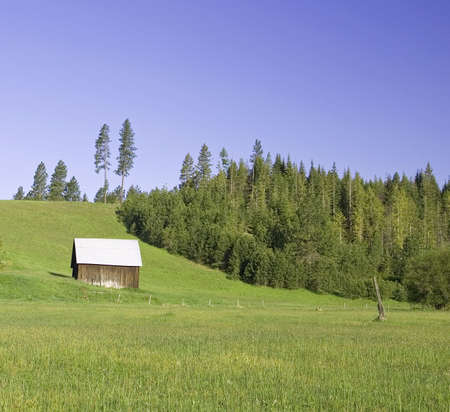 A barn at the base of a hill on a sunny day. photo