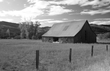 Black and white image of an old barn. photo