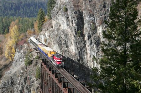 A small tour train travels through the mountains on a scenic journey.