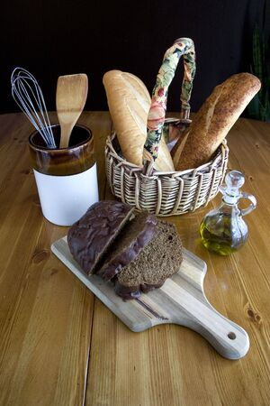 cruet: Various breads displayed on a table with a jar and a cruet of olive oil.
