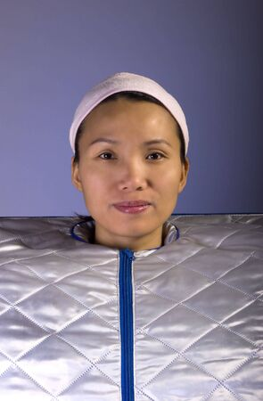 Woman poses in a portable sauna in a studio.