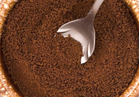 coffee grounds: Looking down at dry coffee grounds and a spoon.