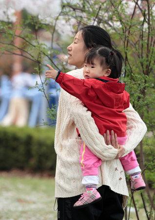 Korean mother carries her daughter in a park in Seongnam, Korea. 04/11/2008 Editöryel