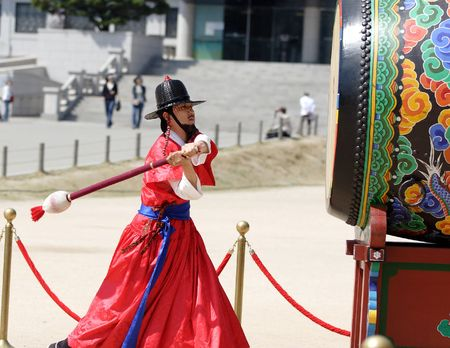 Korean man in traditional costume beats the drum to signal the changing of the guard at Kyoungbok Palace in Seoul, Korea. 04/16/2008