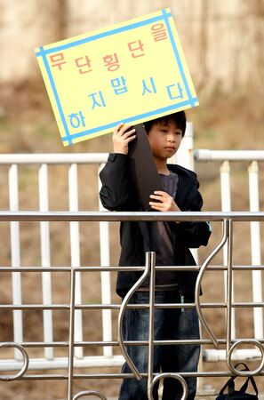 inform information: A Korean student holds a sign informing pedestrians about the dangers of jaywalking in Ichon, Korea. 04042008