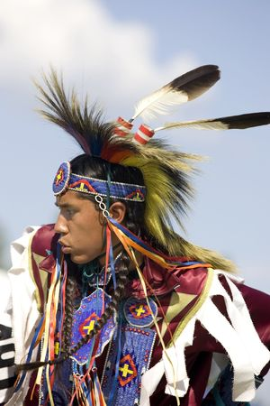 A side view of a young native American teen in full dress participates in the dance at the Julyamsh Powwow in Post Falls, Idaho. 07252009