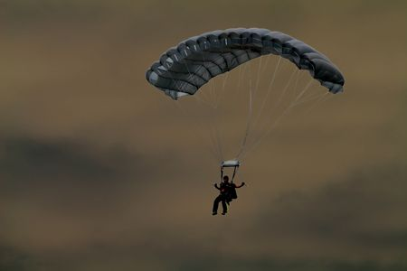solarize: A skydiver soars through the sky in this solarized