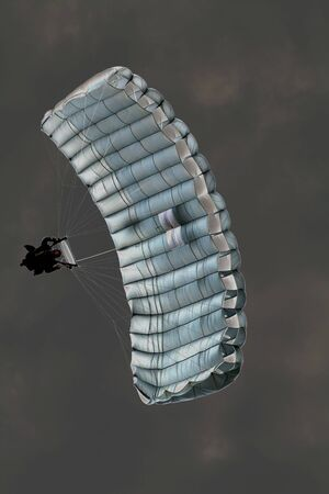 A solarized image of a sky diver with his chute deployed.