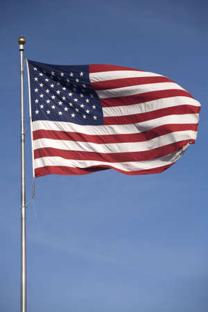 greatly: The American flag flying greatly against a bright blue sky.