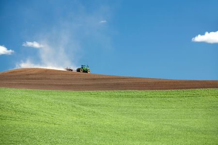 A tractor moves its way across a field in the palouse region near Steptoe, Washington. Stock Photo