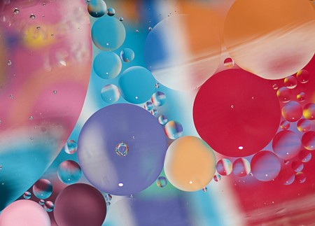 Drops of oil in water above a multicolored background. Stock Photo - 7618010