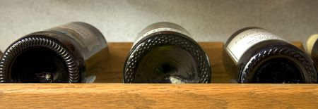 A panoramic image of wine bottles on a shelf.