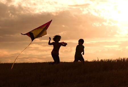 Two kids flying a kite at sunset invoke childhood memories. Banque d'images