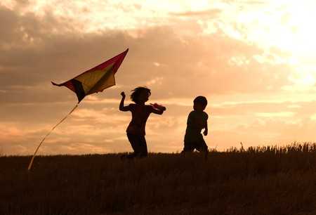 Two kids flying a kite at sunset invoke childhood memories. Stock Photo