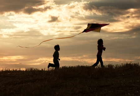 Two children enjoy flying a kite during sunset. Stock Photo