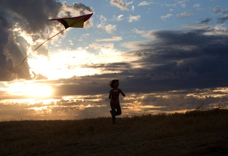 A young girl enjoys a carefree evening flying a kite. photo