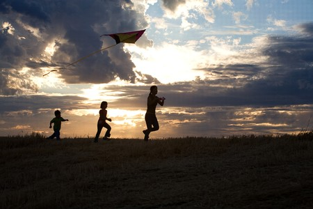 A mother and her two children run with a kite during sunset. Stock Photo