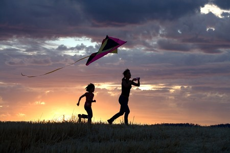A mother runs to fly a kite with her daughter behind her.