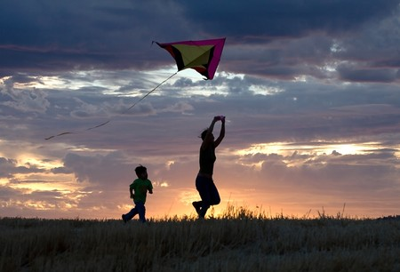 pursue: A mother runs with a kite while the son follows behind during sunset. Stock Photo