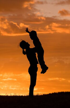A mother holds her little sun up in the air during sunset. Stock Photo - 7748949
