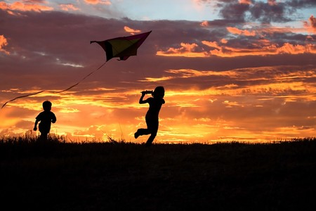 A brother and sister getting a kite to fly suring sunset. Stock Photo