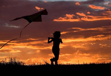 A young girl runs to try and fly her kite at sunset. photo