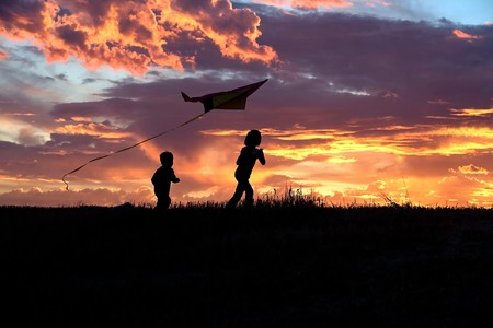 A girl flies a kite at sunset while her brother runs after. Stock Photo