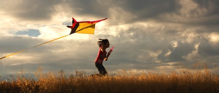 A panorama of a girl happily flying her kite.