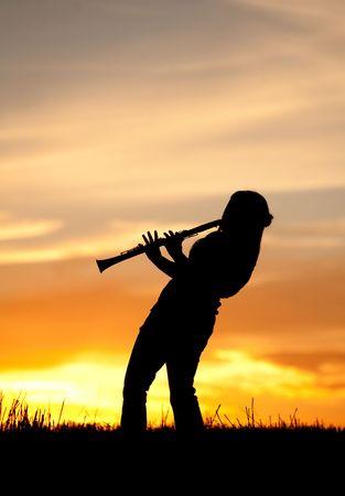 clarinete: Una mujer de silueta toca el clarinete al atardecer.