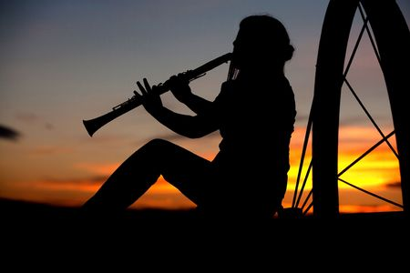 A silhouetted woman plays the Clarinet at sunset.